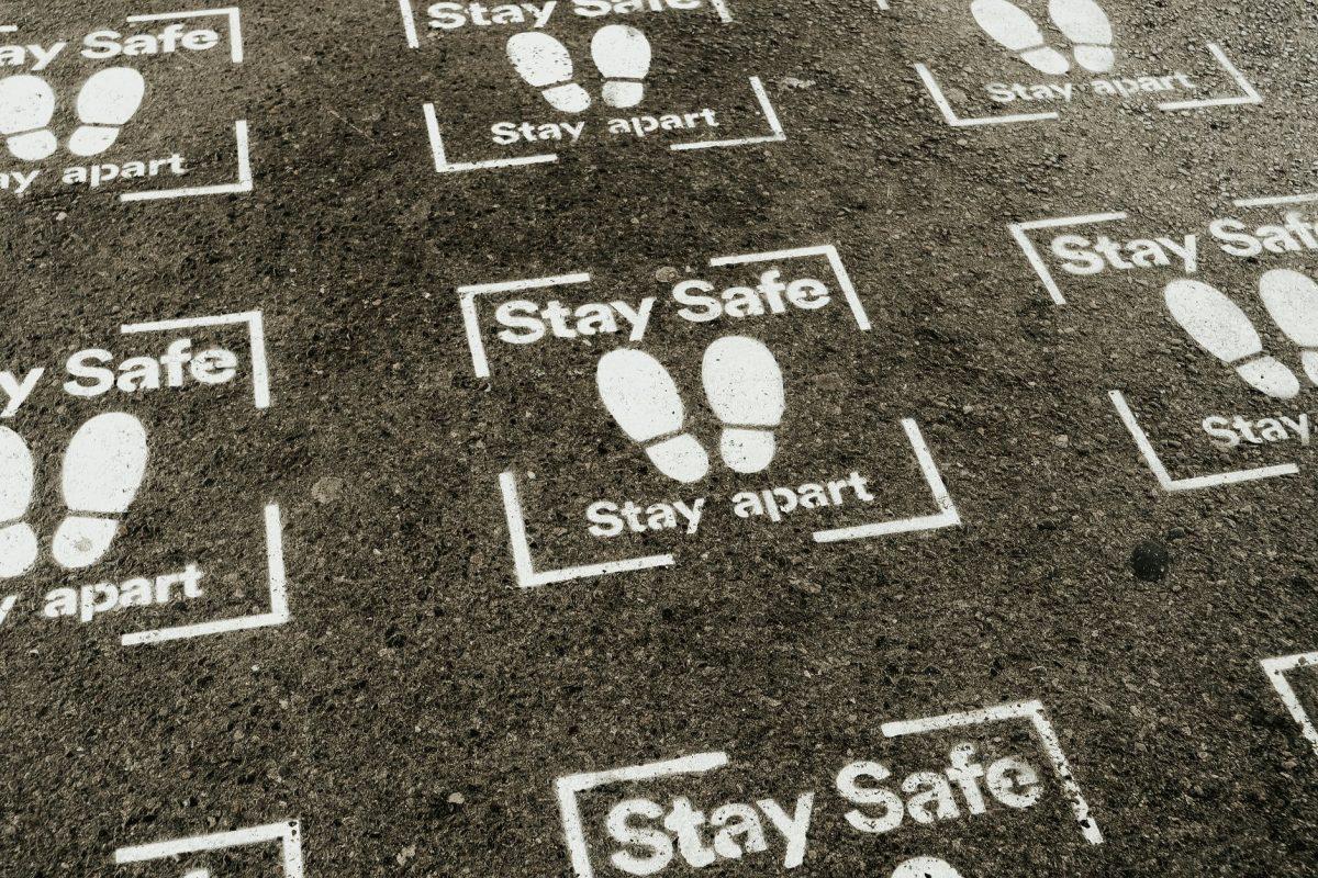 asphalt road with inscription stay safe stay apart