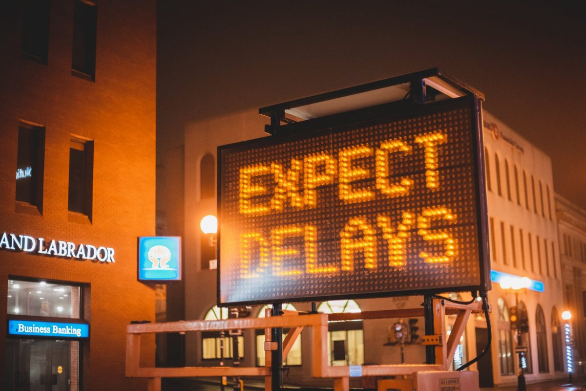 glowing signboard with inscription placed on city road in evening time